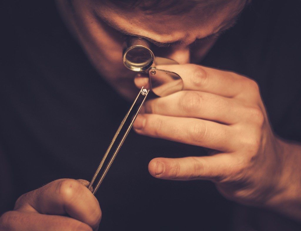 a man inspecting a diamond