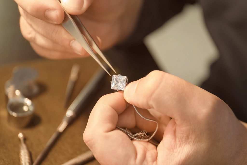 a man customizing a diamond necklace