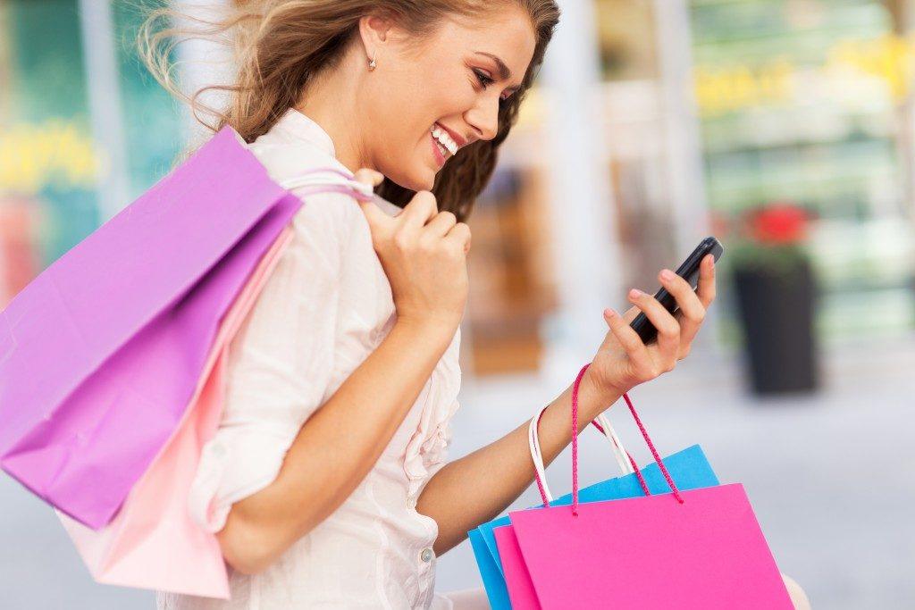 woman with shopping bags, looking at phone