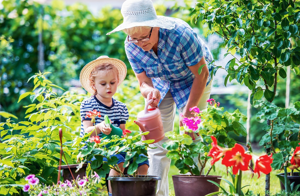 Grandmother and granddaughter watering plants