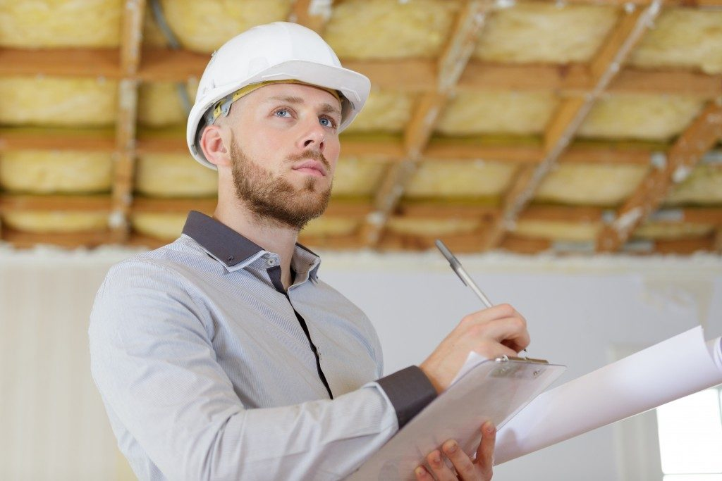 Construction worker inspecting house