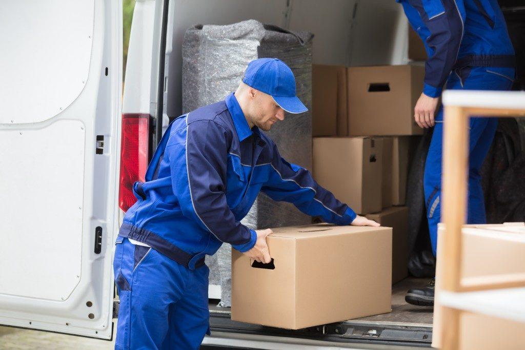 Mover placing cardboard box inside van