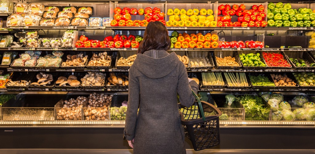 Woman holding basket while grocery shopping