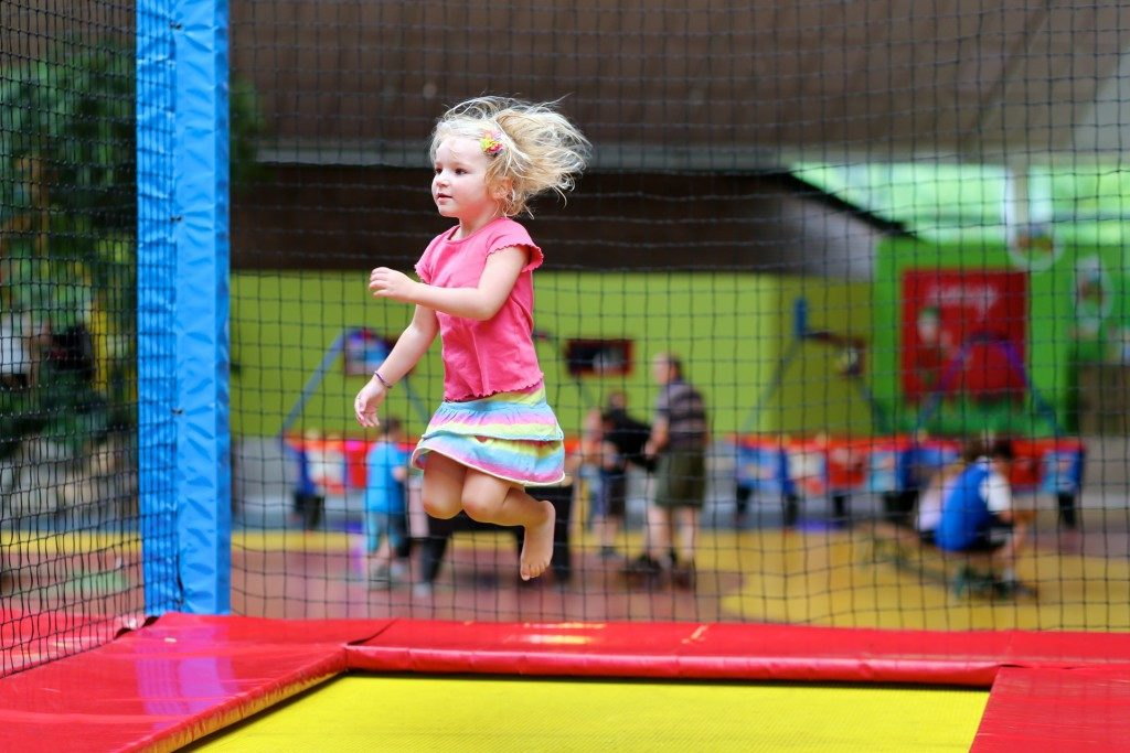 Little child jumping at trampoline in indoors playground