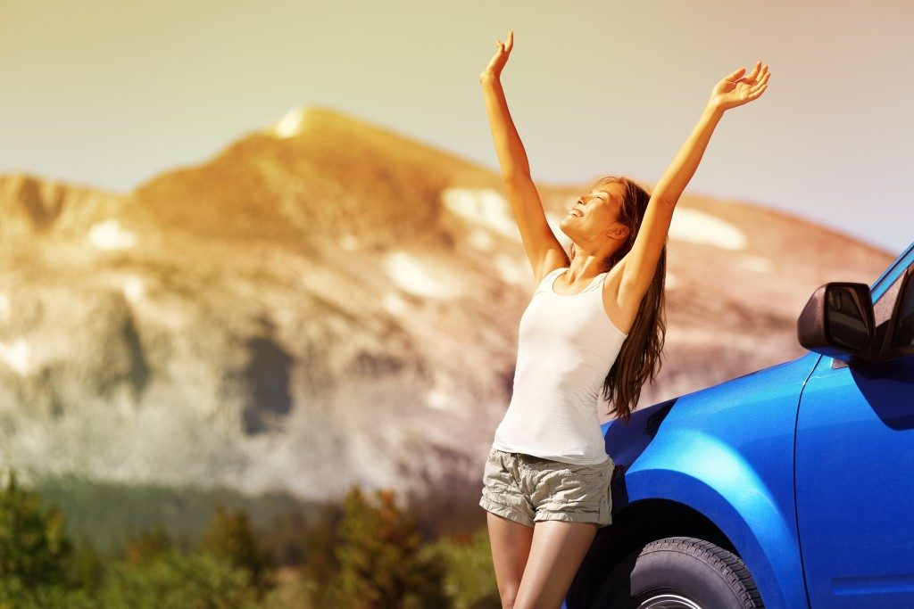 Happy woman feeling the air beside her car