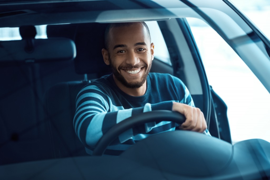 man smiling while driving car