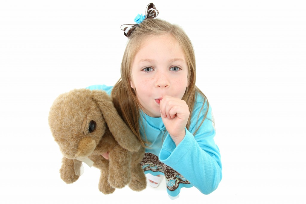 girl carrying a teddy bear and sucking her thumb