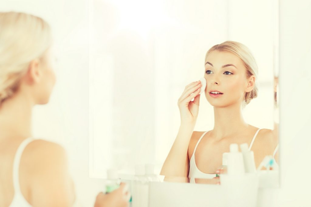 young woman with lotion washing face at bathroom