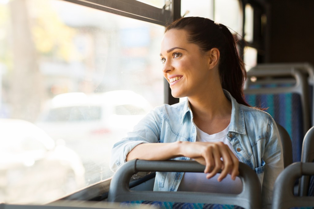 woman looking out the window riding a bus