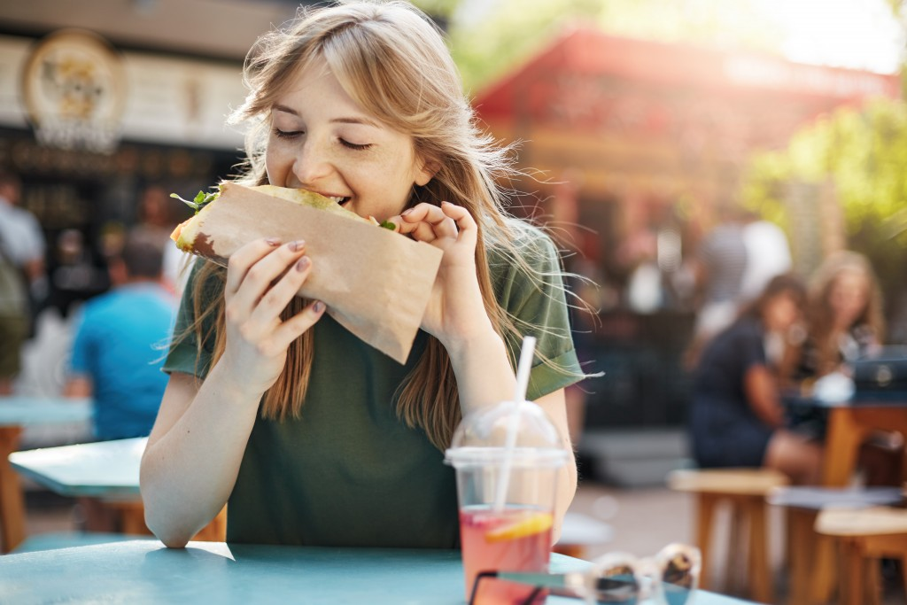 woman eating in a food park