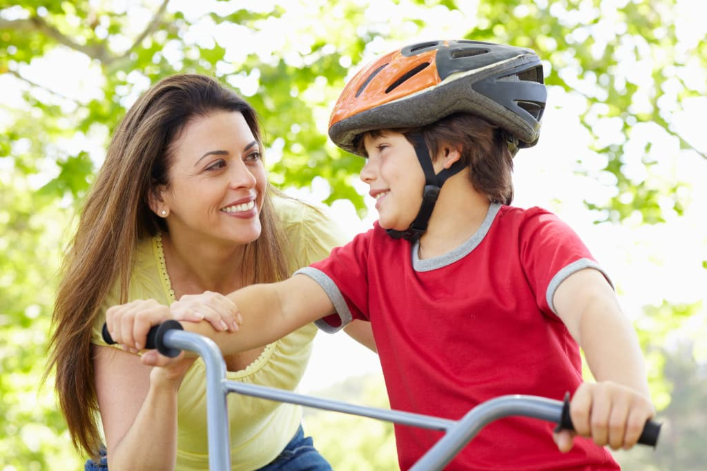 mother teaching son to bike
