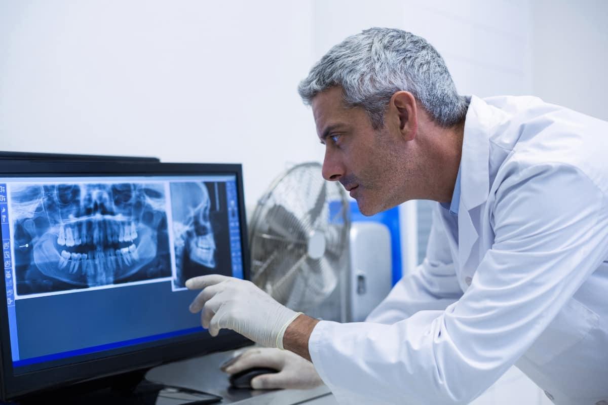 dentist examining x-ray results